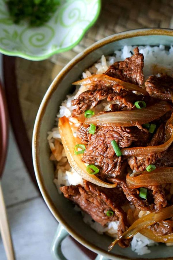 beef with onion on top of rice in a bowl with chopsticks on the side