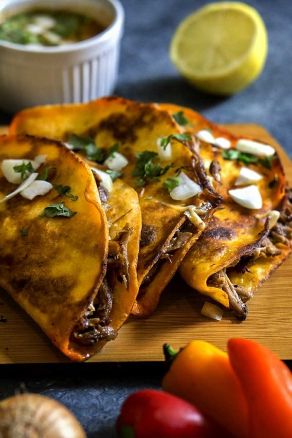 tortilla stuffed with beef and cheese on a board on top of table