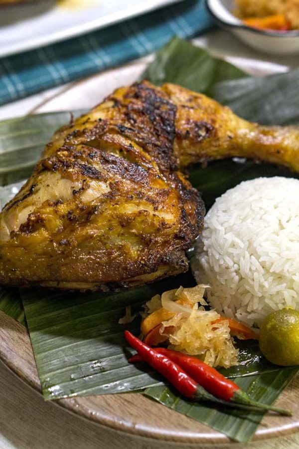 grilled poultry with rice in a plate on top of table