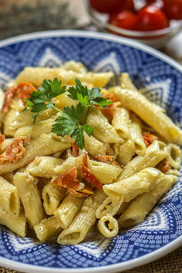 pasta with tomatoes and parsley in a bowl on top of tabe