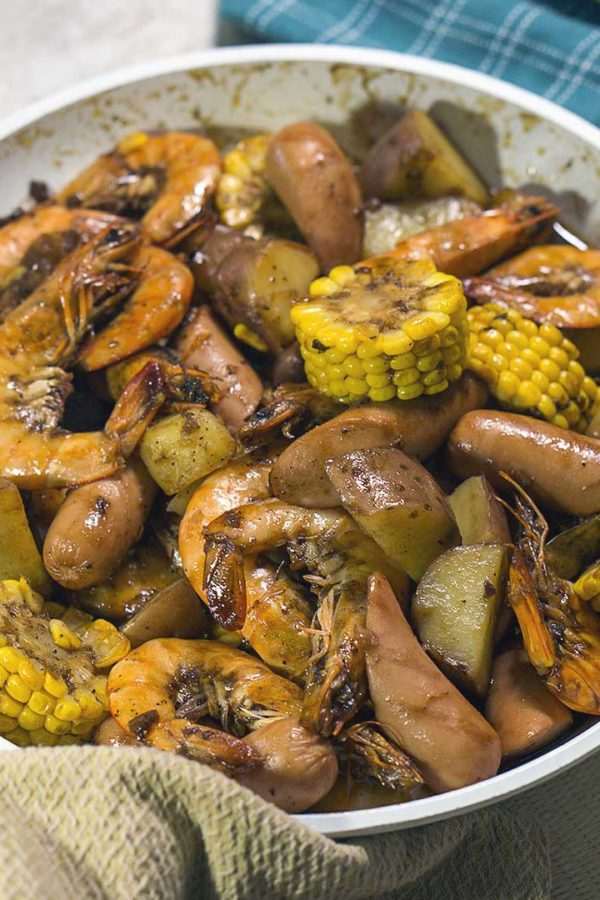 seafood with corn and potatoes in a pan