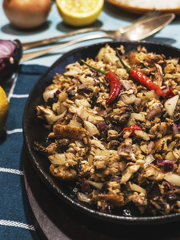 sisig milkfish in a sizzling plate on top of table